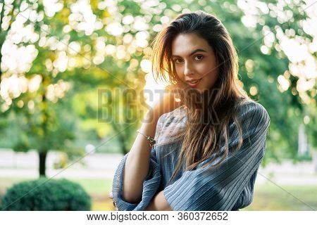 Young Beautiful Woman Outdoors On Green Background Summer Nature. Close Up Portrait