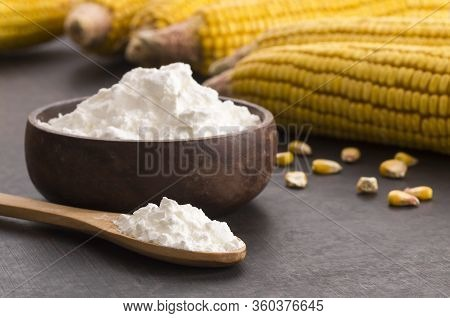 Corn Starch In Wooden Bowl And Spoon With Dried Corn Groats, Kernels On Rustic Table. Corn Ingredien