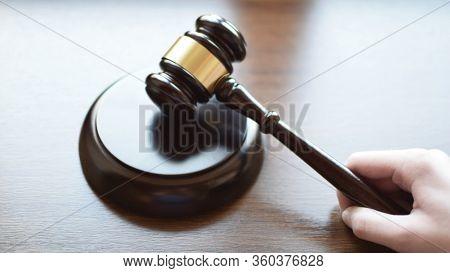 Hand Holding Gavel On Sound Block On Dark Brown Wooden Texture Background, Copy Space. Justice, Judg