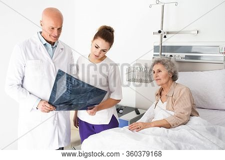 Team Work, Doctor And Nurse Standing In The Ward Near Elderly Patient, They Watching A Picture Of An