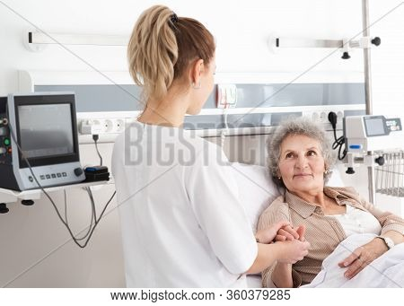 Elderly Woman In A Hospital Ward Receives Nursing Care. Recovery After Surgery, Patient In The Ward
