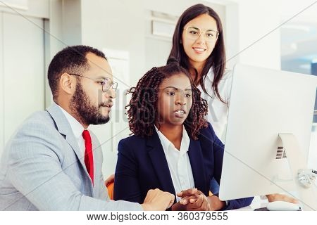 Professional Multiethnic Business Team Working With Computer. Young Business Colleagues Using Deskto