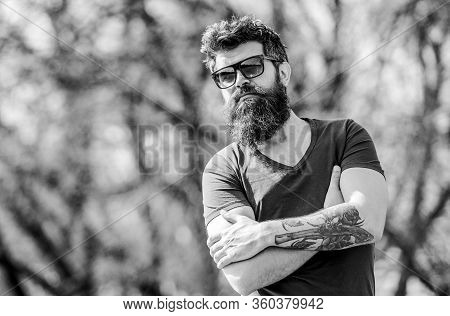 Man Bearded With Sunglasses Nature Background. Bearded Hipster Brutal Man Wear Protective Sunglasses