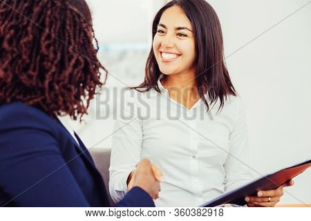 Cheerful Businesswomen Shaking Hands. Happy Young Businesswoman Holding Folder And Greeting Female C