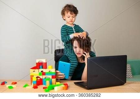 Work At Home. The Child Freaks Out And Climbs Mom Around The Neck While The Woman Is Working On The
