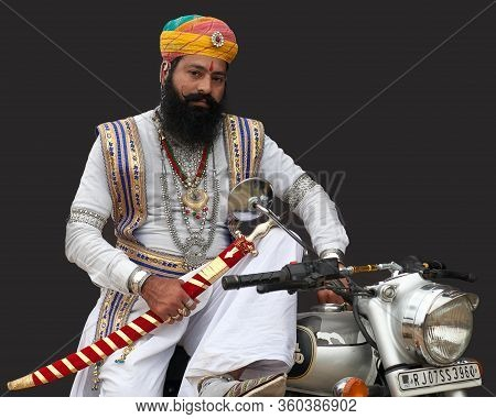 Bikaner, India - January 12, 2020: Rajasthani Handsome Man In Traditional Clothes With Motorbike Pos