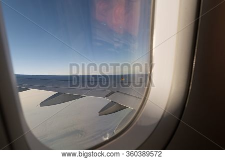 In The Air, View Of The Airplane Wing With Horizon Of Dark Blue Sky And Clouds Background In Sunrise
