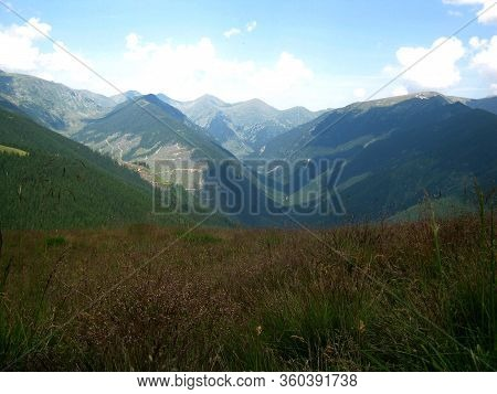 The Magnificent Mountain Landscape Of The Carpathians. Rocky Cliffs And Grassy Hills Under A Cloudy