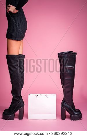 The Girl Stands In Black Jackboots On Her Feet On A Pink Background. In The Middle There Is A Bag Fr