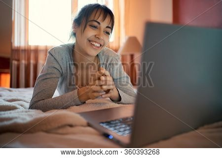 Happy Woman Lying On Bed At Home And Chatting With Boyfriend, Having Video Call On Laptop Computer,