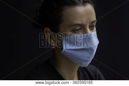 Worried Young Woman Wearing Medical Face Mask, Studio Portrait. Woman Wearing Face Mask During Coron