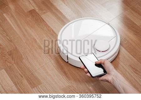 Housewife Using Mobile To Control Robotic Vacuum Cleaner. Robot Controlled By Voice Commands To Dire