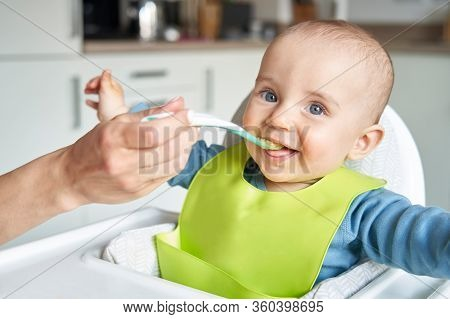 Portrait Of Smiling 8 Month Old Baby Boy At Home In High Chair Being Fed Solid Food By Mother With S
