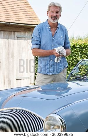 Portrait Of Mature Man Restoring Classic Sports Car Outdoors At Home