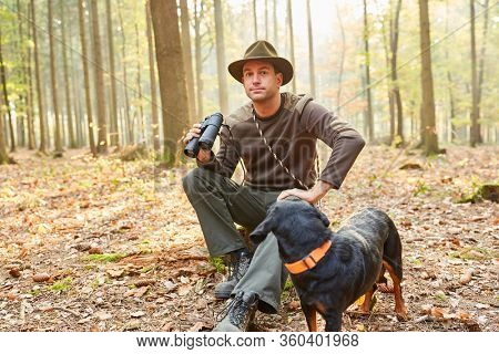 Forester or hunter with a hound as a hunting dog and binoculars in the forestry area