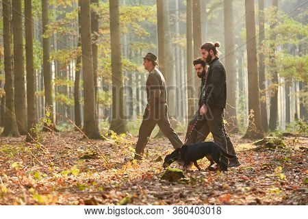 Three hunters or foresters walk with a hound as a hunting dog in the forest