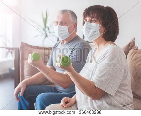Coronavirus CoVid-19 Couple old aged senior people at home with seasonal cold illness disease doing exercise. Elderly couple in medical masks during the pandemic Sport