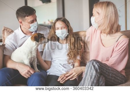 Happy family at home. Mom dad and child on sofa during the pandemic coronavirus Quarantine