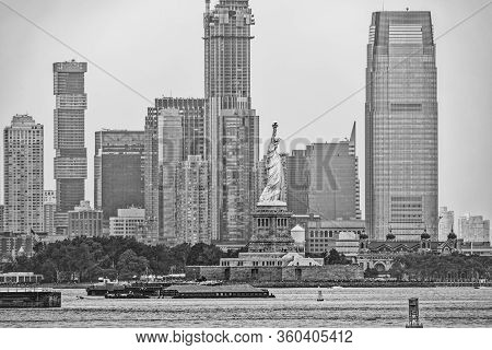 Statue Of Liberty On Liberty Island During The Gloomy Weather In New York With Jersey City Panorama