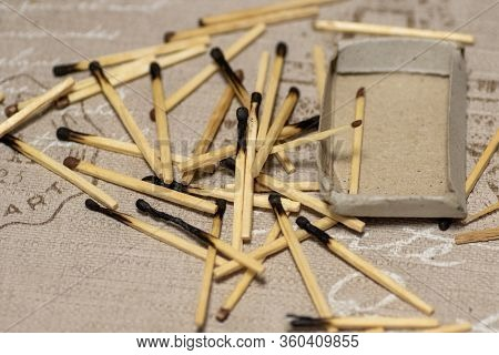 Top View Of A Pile Of Burnt Matches And An Empty Box Of Matches. Background. A Lot Of Burnt Matches