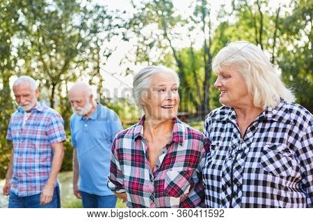 Two senior women talking while walking with friends in nature