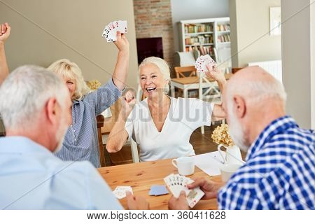 Group of seniors has fun playing cards together in retirement home
