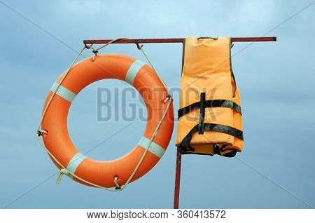 Life Preserver And A Life Jacket On The Bar On The Background Of Blue Sky