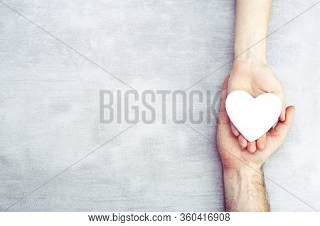 Male And Female Hands With A White Heart, Health Care, Love And Family Insurance Concept, World Hear