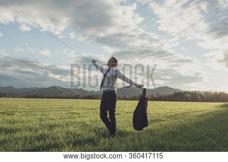 Successful Young Businessman Standing In Green Meadow Under Evening Sky After A Long Day At Work, Re