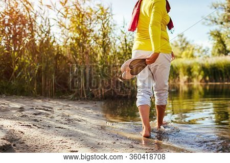 Middle-aged Woman Walking On River Bank On Spring Day. Senior Lady Having Fun In The Forest Enjoying