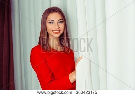 Portrait Of A Young Smiling Woman  In Red Dress Opening Curtains. Indoors Shot, Horizontal Image