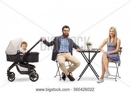 Young parents with a baby in a pushchair sitting at a table isolated on white background