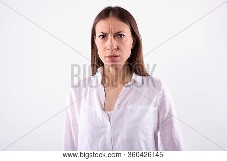Young Caucasian Girl With Brown Long Straight Hair , Dark Eyes In Casual White Shirt Looking Incredu