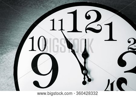 Black And White Wall Clock Showing Five Minutes Until 12 Oclock
