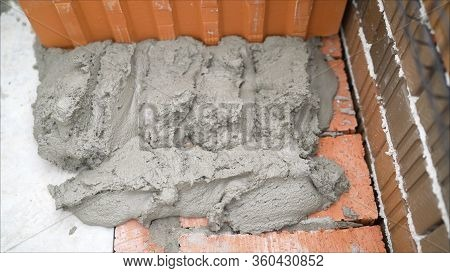Industrial Worker Using Trowel And Tools For Building Exterior Walls With Bricks And Mortar. Stackin
