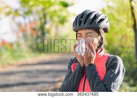 Cough in tissue covering nose and mouth when coughing outside as COVID-19 hygiene guidelines for Coronavirus spread prevention. Biking cyclist girl sneezing in paper outside.
