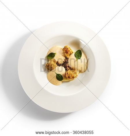 Scallops in crispy breading top view. Served roasted seafood dish with potato mousse and fish ragout in plate. Gourmet culinary, gastronomy. Restaurant food portion, cooked main course