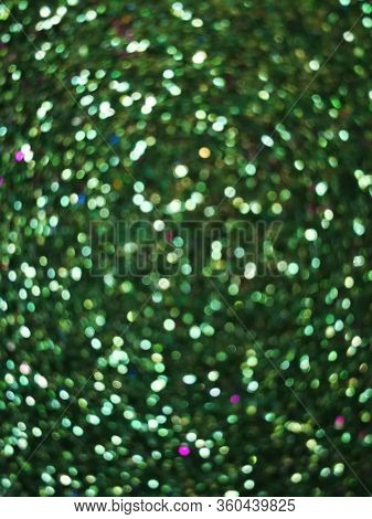 Glitter and shiny lights on green background