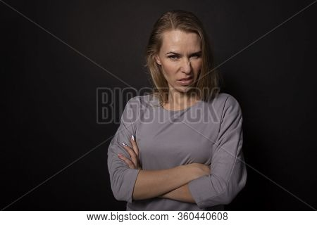 Beautiful Young Caucasian Woman Transsexual With Fair Hair Standing With Arm Crossed. Dislike Disgus