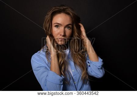 Attractive Young Caucasian Woman With Fair Long Curly Hair In Casual Blue Shirt Looking Seriously An