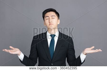 Confused Young Businessman Shrugging Shoulders And Showing Helpless  Gesture
