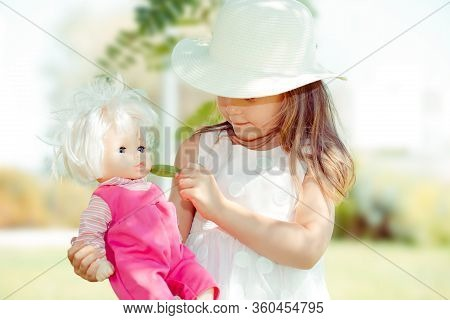 Girl Feeding Her Doll. Closeup Portrait Head Shot Of Playing Giving To Eat To Her Doll Toy Looking A