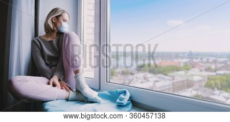 Young woman is sitting  in medical mask on a sill and look at window. Quarantine, isolation, self-isolation.