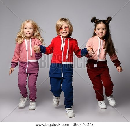Full Growth Portrait Of Three Frolic Playful Kids Blonde And Brunette Girls And Blond Boy In Modern