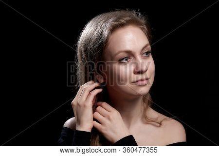 Beautiful Gentle Girl With Long Blonde Hair On Dark Background. Romantic Portrait In Renaissance Sty