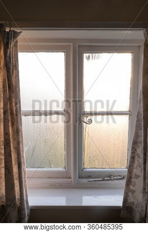 Substandard Housing In England, Uk, With Condensation On Old Window With Curtains