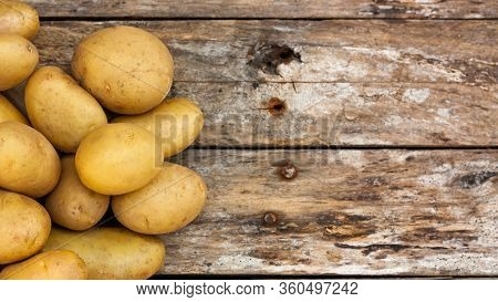 Raw Uncooked Organic Potatoes Over Natural Weathered Wooden Boards. Top View. Copy Space.