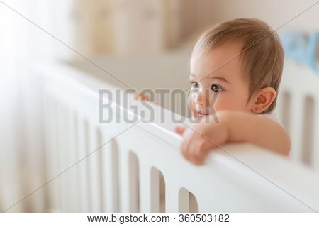 Portrait Of Cute Baby Standing In Crib. Baby Girl Stand Alone In Crib. Happy Baby Girl In White Baby