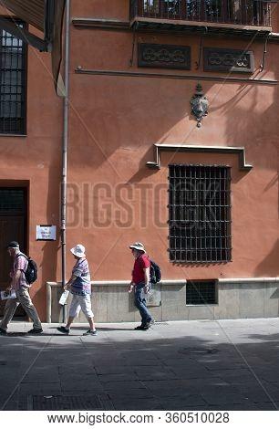 Granada / Spain / 10-11-2019: Tourists Walk By A Fine Old Building At Plaza Bib Rambla On A Late Sum