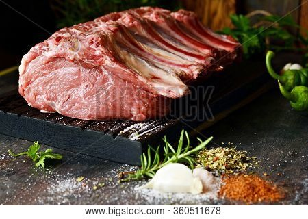 Fresh Raw Pork Loin On The Bone On A Wooden Board With Herbs, Spices And Sea Salt. Meat For Grilling